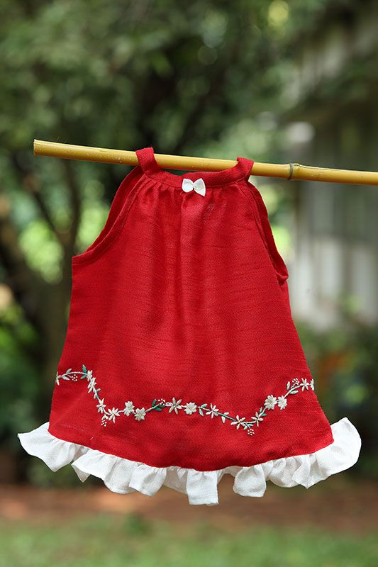 Elegant sleeveless red frock with a beautiful contrasting white colour bow in the middle. Made from faux silk this beautiful dress hand embroidered border adorned with small white flowers add to the beauty of your little doll.