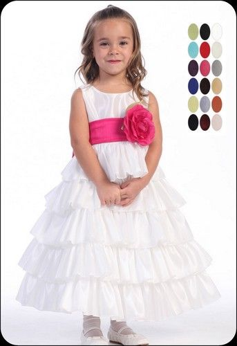 Tiers of shimmering taffeta tumble down an elegant white flower girls dress fashioned with a sleeveless bodice, a beautiful bloom adorns the empire waist that cinches back with a sash in your desired color.