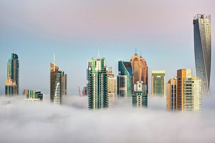 "Picture by BERNARD MENETTRIER DE JOLLIN: Colorful buildings of the Dubai Marina emerge on top of the Christmas morning fog in this 24 December 2012 Dubai picture titled ""Emerging""  Location: Dubai Marina, UAE Creation: 2012"