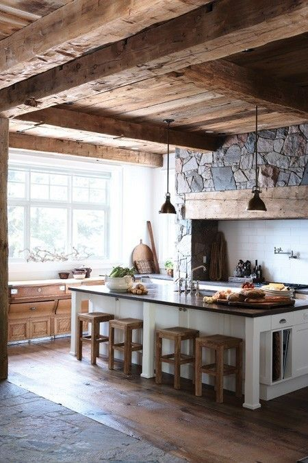 Man cave kitchen - love the rustic wood beamed ceiling and stonework. The kitchen has a great white island with dining stools. side storage for pans. Big window keeps it airy.