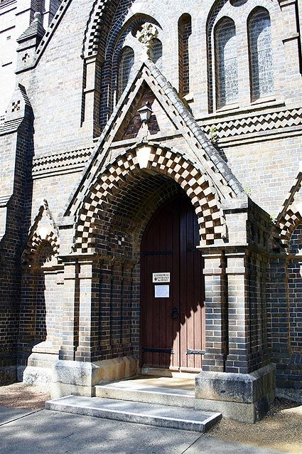 "The Tower and West Door of St Peter's Cathedral, Armidale. ""Advancing series of piers and buttresses, arched wall panels receding in three or four planes, course upon course of boldly dentilled arches, indented gables, bands of projecting diagonally laid bricks, and plain horizontal weather moulds are thrown into heightened relief by the bright New England sunlight.""  J. M Freeland"