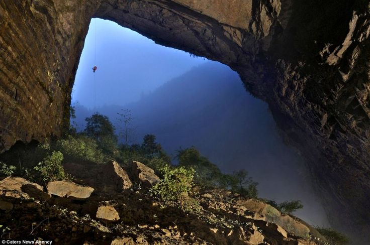 An intrepid cave explorer ascends a rope hanging from the Niubizi Tian Keng. This photograph is one of the first-ever images taken of one of a cave so large it has its own weather system