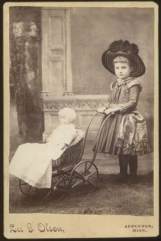 Cabinet-card format albumen print of a happy young girl with large doll in baby carriage