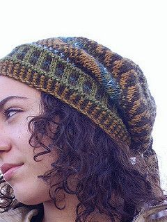Knit in the round from the bottom up, with some interesting details. The bottom edging is a 2 color 1x1 rib. At the top, the decrease is incorporated first in the stranded colorwork. Then it moves into one color, and a rib st. The tassels really make the hat- include as many colors as you wish.
