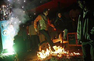 """An Iranian couple jumps over a bonfire during """"Chaharshanbe Suri"""" in the Darakeh mountains north of Tehran :!"""