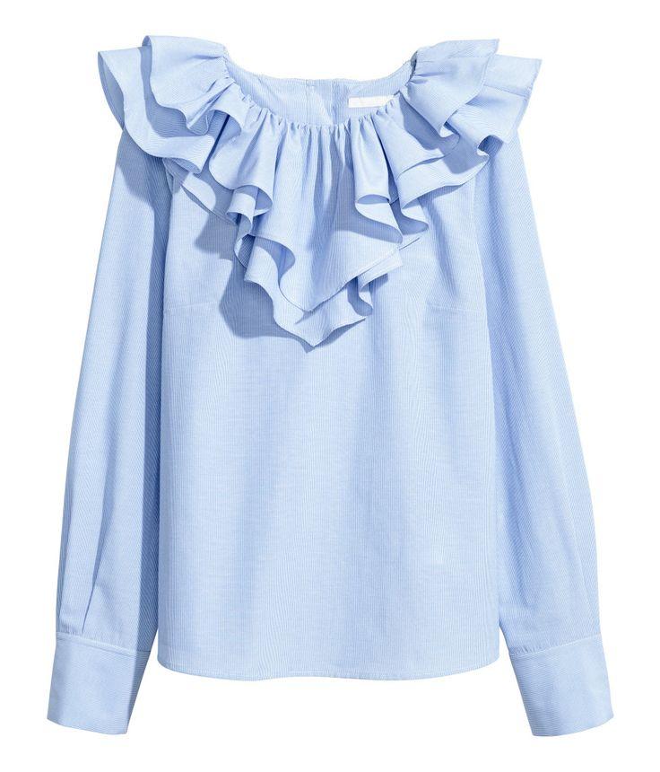 Blå/Vit randig. En smalrandig blus i vävd bomullsblandning. Blusen har dubbla volanger kring halsringningen vilka fortsätter ned på bakstycket. Knäppning i