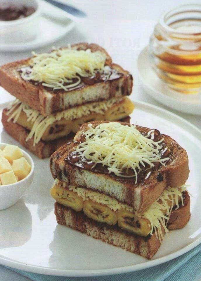 :: Sandwich Roti Lapis Pisang Keju ::   Lapis Pisang Coklat Keju  Bahan:  - 4 lembar roti tawar, yang dibentuk sesuai selera - 4 buah pisang raja matang - 2 sendok makan mentega untuk memanggang pisang - 50 gram keju cheddar yang sudah diparut - 2 sendok makan nutela coklat  Cara Membuat:  - Panaskan 2 sendok makan mentega pada wajan anti lengket, lalu panggang pisang sambil ditekan-tekan pipihkan, bolak-balik sampai empuk, kemudian angkat. - Taruhlah lembaran roti tawar pada piring saji…