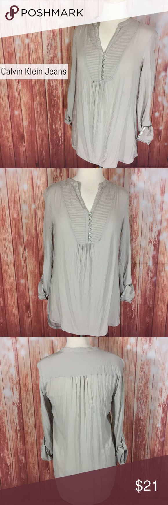 """Calvin Klein Jeans M GRAY RollTab longsleeve Tunic Calvin Klein Jeans pleated Roll-Tab long sleeve tunic top Size Medium (measurements in comments) Gray color Soft, light weight material  1 Small """"pull"""" on bottom back NO OTHER DEFECTS  •This Top is very versatile! Wear with boot cut jeans & black boots! •Wear with skinny jeans & booties for a night out! •Wear with a gray or black maxi skirt & Ballet flats for a relaxed but chic look! ~~~~~~~~ Pet friendly home  Smoker but not in the home…"""