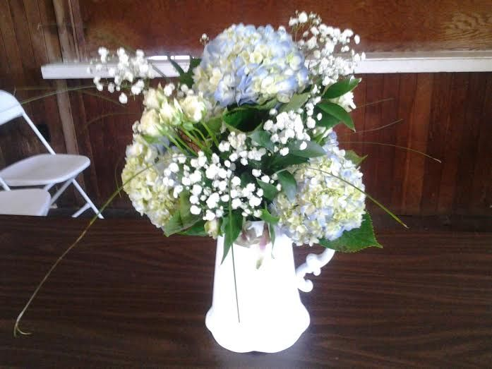 For the food table we took an old Picture and filled it with the Blue Hydrangea, Baby's Breathe, Bear Grass, White Alstroemeria, and added some green leaves. Turned out amazing.