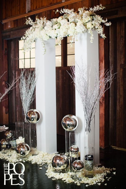 Your guests will be dazzled with this contemporary alter created from white columns, clear vases, silver branches, white flowers and petals and silver globes. #timelesstreasure