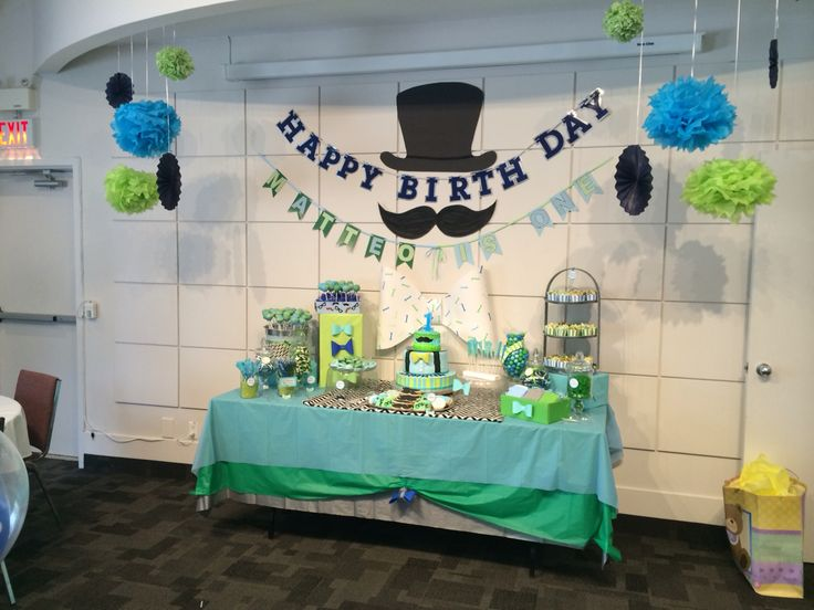 DIY BIRTHDAY PARTY - Matteo's first birthday  Top hat, moustache, oversize bow with no. 1 print, paper fans, puffs, happy birthday garland, Matteo is one garland, table cloth pickup with bow detail (silver, blue, green, black & white chevron)  Decor by Rosa Tubman