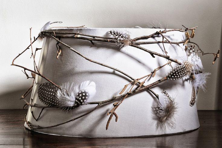 Plumes et branches empreintées à Yggdrasil, l'arbre cosmique autour duquel s'enroule le rituel du printemps.  Abat-jour de forme trapézoïdale en pur coton de couleur gris clair recouvert de branchages et de plumes naturelles de pintade et d'oie Dimensions: Ø bas: 30 cm H: 23,5 cm Pour douille E27  Description: - structure métal époxy blanc recouverte de polyphane et d'un tissu de coton gris clair - plumes naturelles de pintade et d'oie  Personnalisation(sur devis): dimension ...
