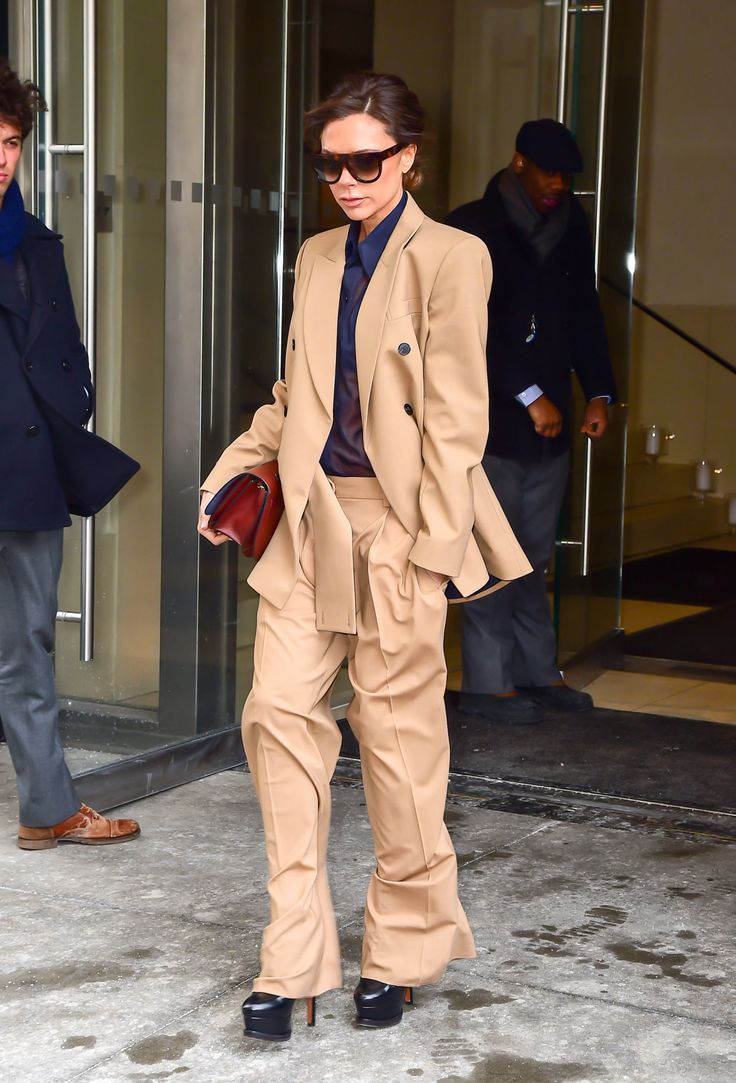 Victoria Beckham rocked a beige trouser suit and sunglasses with sky high heels.