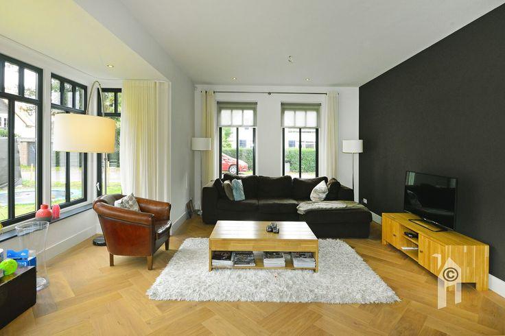 De woonkamer baadt aan alle kanten in daglicht. Leuke roeden-verdeling in de raampartijen