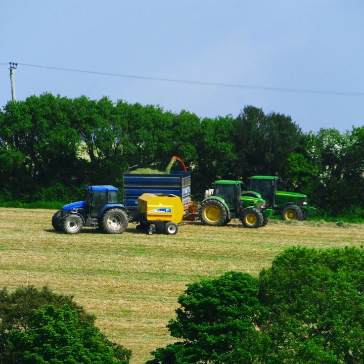 Three Tractors Working In The Evening Sun