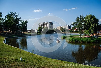 A lake in an urban park wit a swan boat floating. High rise apartment buildings in the background.