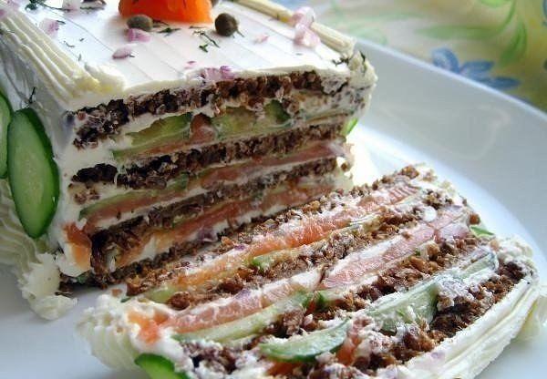 Бутербродный торт с копченым лососем и мягким сыром.   Красивый и невероятно вкусный праздничный бутербродный торт с хрустящими огурцами и копченым лососем, пропитанный и украшенный взбитым сливочным сыром.   Вам потребуется:   Хлеб цельнозерновой 4 ломт.  Сыр мягкий сливочный 340 г  Лук красный 1 ст.л  Укроп 3 ст.л  Каперсы консервированные 1 ст.л  Лимонный сок 1 ст.л  Соль щепотка  Перец свежемолотый по вкусу  Лосось копченый 200 г  Огурец 2 шт.   Как готовить:   1. Разделить крем-сыр на…
