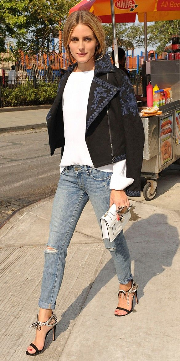 Olivia Palermo wearing an embroidered moto-style jacket, white blouse, ripped cuffed jeans, and ankle strap embellished heels