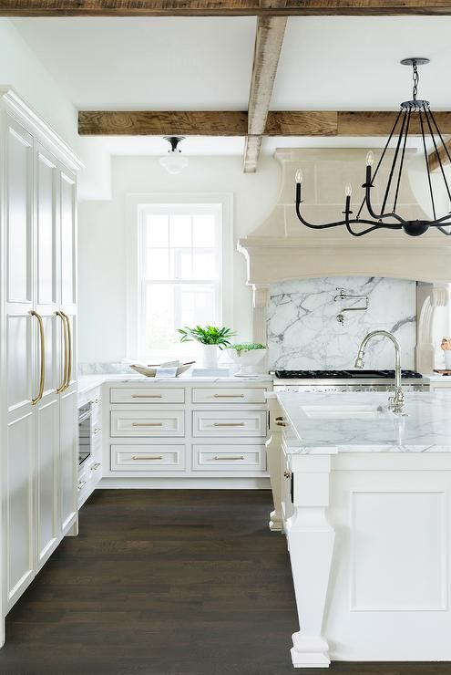 An iron chandelier lights a white kitchen island fitted with white legs and a gray and white marble countertop finished with a prep sink and a polished nickel gooseneck faucet.
