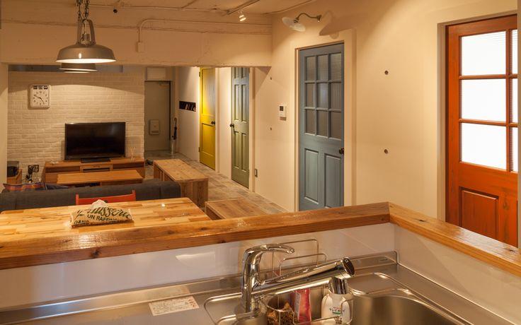 """3LDKを2LDKに再構成し、玄関からキッチンまで直線に抜けた間取りにしたことで、より広がりのある空間に。""""アメリカンポップ""""というデザインコンセプトの通り、映画のワンシーンのようでありつつ、どこか可愛らしさも感じさせる雰囲気です。renovation-selectshop-02"""