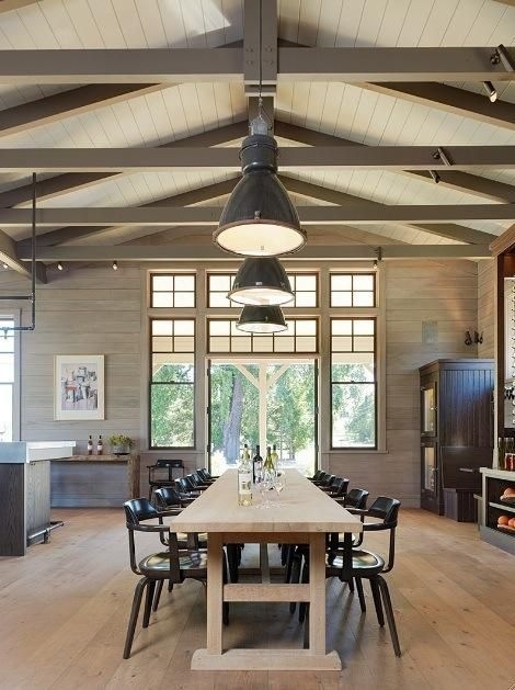 In the interiors, Wick used the one-room schoolhouse as inspiration, relying on a soft color palette with natural earth tones to provide a seamless transition for the indoor-outdoor spaces. Vintage black industrial lights suspended above an oak trestle farm table. The 1950s dining chairs are by Walter Gropius, retrieved from a school library.