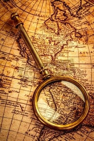 Vintage still life. Vintage magnifying glass lies on an ancient world map mural