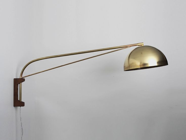 The Arc Wall Lamp features an American black walnut mounting bracket and a spun brass half dome shade; $480.