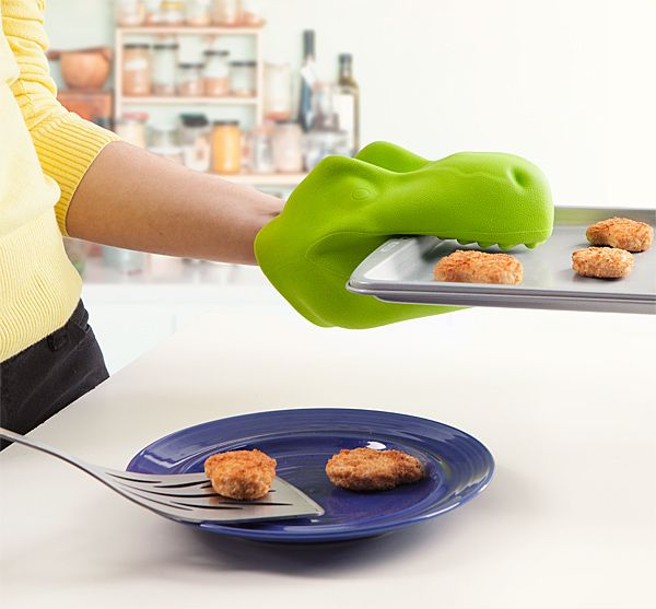 """ThinkGeek has created a ferocious T-Rex Oven Mitt that fits most adult human hands and comes with built-in ridges to help grip your prehistoric pans."""
