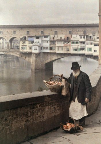 Florence, Italy. A man sells pomegranates along the Arno river. Photographer: JULES GERVAIS COURTELLEMONT