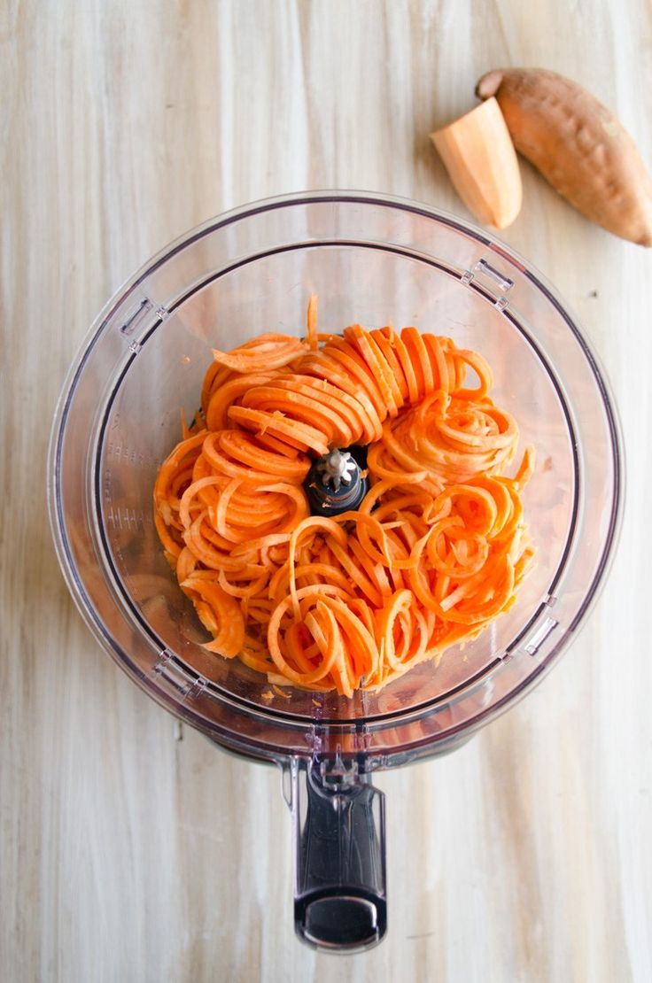 A top down view of a food processor filled with spiralized sweet potato for Crispy Southwestern Sweet Potato Fries.