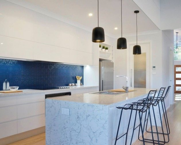 Meet White Attica, a new surface inspired by classic natural marble. The blue backsplash is particularly unique and complements the intricate veining on the island. Design by Hotondo Homes