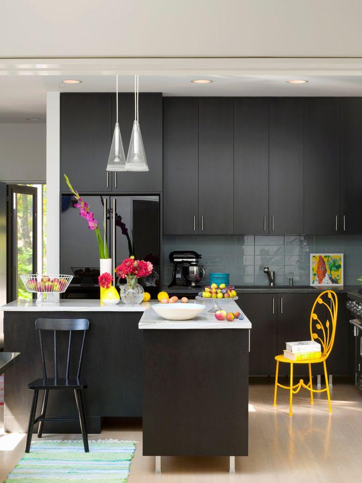 Cozinha apresenta móveis pretos, pontuada com cores vivas