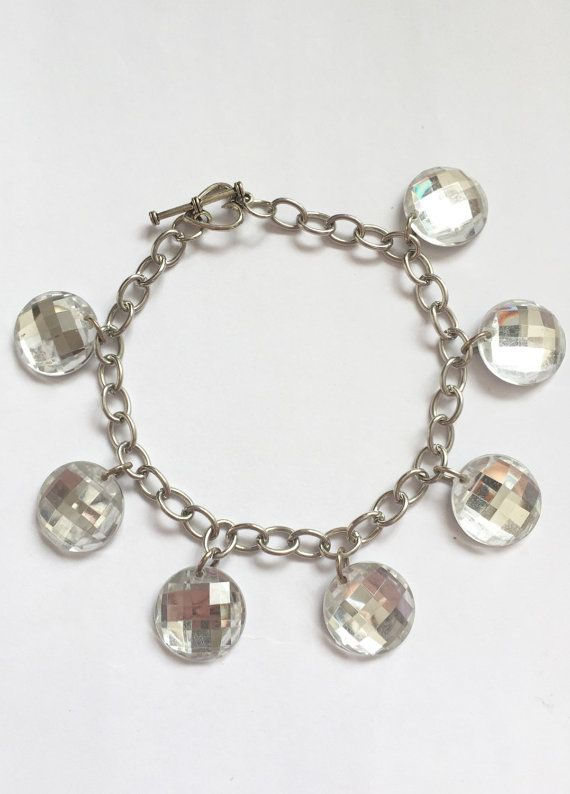 Silvertone chainlink bracelet with clear gem-look charms. Silver backing gives them mirror-like shine. Very sparkly and shiny. Heart-shaped
