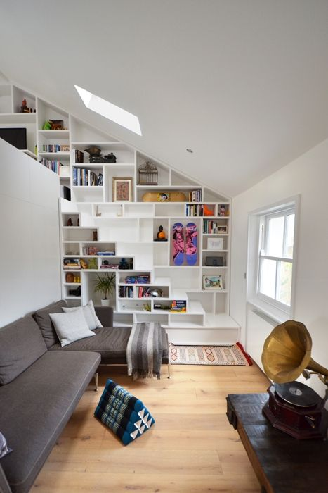 La parete a ridosso del volume centrale è sfruttata come libreria, così come la scala che porta al soppalco