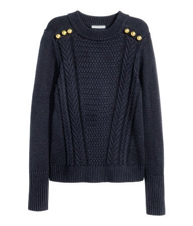Long-sleeved sweater with a pattern-knit front section and decorative buttons on shoulders.