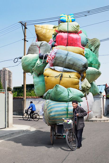 The bicycling men of China are put on display in a new series, Totems, by French photographer, Alain Delorme.    In the 15-part photo series, Delorme has captured the men carrying huge loads (totems) of cardboard, water bottles, fabric etc, while cycling the streets of Shanghai.