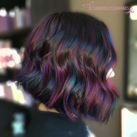 """✨ """"Oil Slick"""" Balayage ✨ Such a fun color! More multi-tones please!!  In this technique I used thick slices to balayage underneath her hair with @colormebykm Up to 7 lightener (with Olaplex) then used 4 custom @Joico vivids (used Magenta, Indigo, Anethyst, Peacock Green, Yellow,  Sapphire and Light Purple) all mixed in with @Olaplex step 2. I painted each slice with 2 colors per foil for a more """"holographic"""" or """"oil slick"""" look! #colormebykm #oilslickhair #galaxyhair #rainbowhair #olaplex..."""