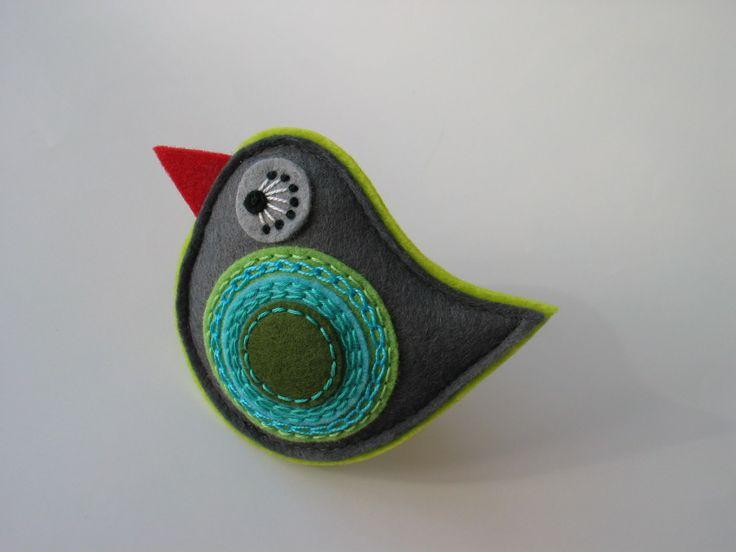 """brož ptáček- """"COLOUR""""; šedá Barevná kolekce broží pod názvem COLOUR je plna veselých a hravých barev..... Brož z plstive tvaru ptáčka, zdobena aplikací sruční výšivkou.Barevná kombinace šedé, tyrkysové a odstínů zelené.Můžete ji použít jako brož na kabát, bundu, svetr, nebo s ní ozdobitkabelku, batoha především obdarovat někoho blízkého. Rozměry: ..."""