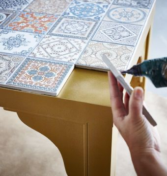 The top of a gold IKEA LACK table is being decorated with decorative tiles.- diy