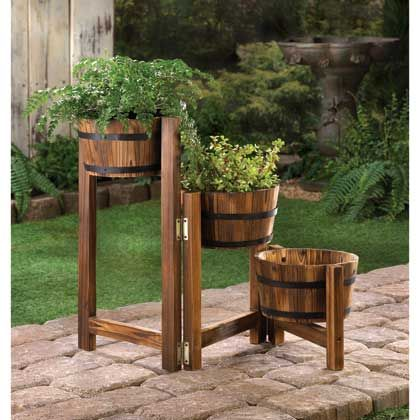 Roll out the barrels and add a dollop of country charm! The simulated fir wood barrels of this planter trio have authentic metal banding and are fastened to sturdy wooden posts. Its hinged tri-level design gives you the freedom to adjust it to fit anywhere in your yard.
