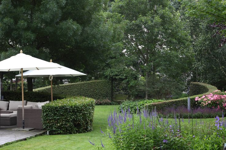 tuin tuinontwerp tuinarchitect hovenier hoveniersbedrijf tuinaanleg beplanting beplantingsplan onderhoud villatuinen loungebank parasol gazon ronde hagen