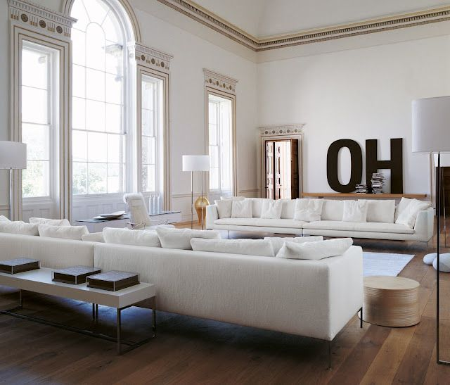 White Living. long white couches, white walls, large windows with natural light. medium/dark wide plank wood floors.