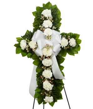 """http://shop.o2o.com/item.php?LBB-tlQ764y6J-52821 Standing Cross White  This white flower standing cross is a thoughtful tribute of sympathy. Created by a florist with white carnations, white wax flower and seasonal greens, in a shape of a cross. Delivered on an easel with a white decorative bow. Measures 18""""H by 30""""L."""