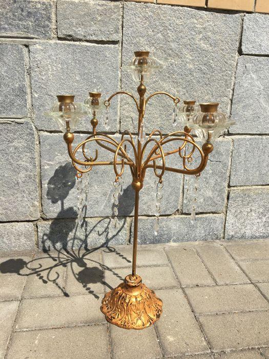 Vijf-arm ijzer kandelaar met 46 kristallen en Murano glas hangers - Italië  Elegante en charmante kandelaar met 36 kristalglas en glas hangers op 16 ijzeren staven.Met 5 x Murano glazen kaars cups en bobeches meesterlijke werkte en bloem gevormd kan die volledig worden gedemonteerd in 10 x stuks.Afmeting: hoogte 56 x 40 cmGlazen bloem: 8 x 8 x 5 cmBase: 15 cmGewicht: 260 kgIn uitstekende conditie; hier en daar wat verlies van verguldsel.Deze ijzeren kandelaar kunnen worden eenvoudig en…
