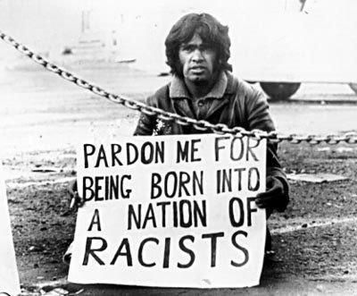"black-australia:  An iconic image showing Aboriginal rights activist, Gary Foley with a placard reading, ""Pardon me for being born into a nation of racists""."