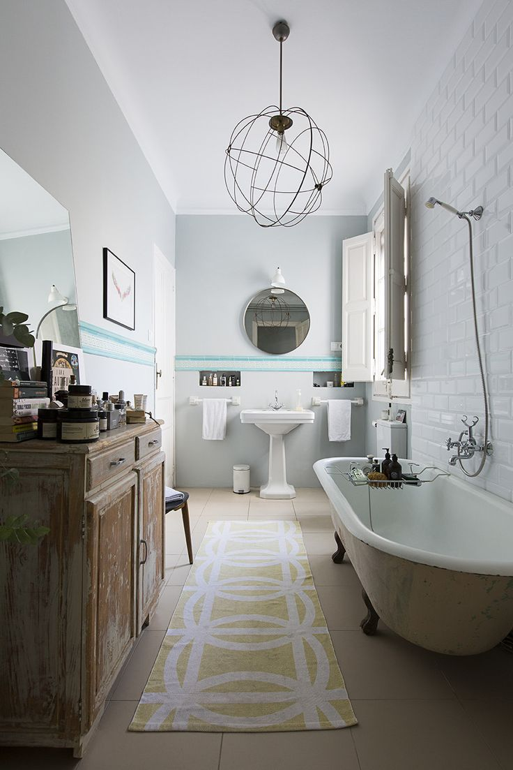 """""""I don't like it when bathrooms look too much like bathrooms,"""" say Kayser. He removed the telltale tiling beneath the Greek-key trim, layering in books, vases, and various soaps and fragrances to build a comfortable rather than sterile atmosphere."""