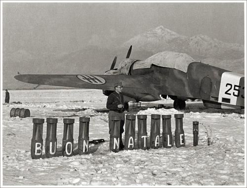 "Christmas in Italy, 1940. An SM.79 is seen behind the bombs, spelling ""Merry Christmas"" in Italian."