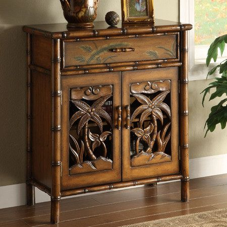 Palm tree storage cabinet perfect in any setting. Honey maple finish with openwork design on door fronts & handpainted leaf motif on drawer front.