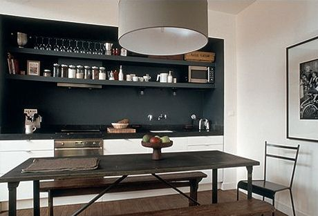 White cabinets, black inset wall and shelves. Drum lampshade, table, benches