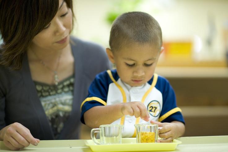 Hälla med kanna. Notera hur läraren sitter på barnets högra sida. När pedagogen presenterar ett materiel för barnet sitter denne alltid på höger sida om denne (den vuxne) är högerhänt och på vänster om denne är vänsterhänt. Detta för att inte skymma presentation för barnet med den dominanta handen. För att litet barn kan man behöva sitta bakom barnet med armarna på var sida om barnet vid presentationen eftersom ett mindre barn har ett kortare koncentrationsspann.